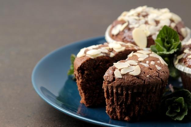 Köstliche, süße schokoladenmuffins mit mandelblüten neben minze und mandeln in einem teller auf einem dunklen tisch.