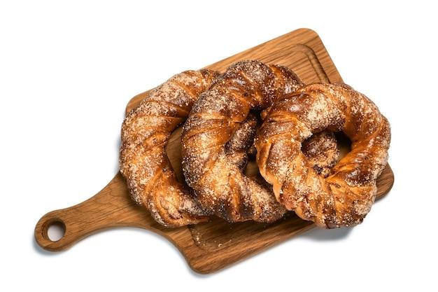 Köstliche süße zuckerringbrötchen auf einem hölzernen schneidebrett