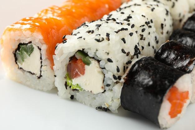 Köstliche sushi-rollen auf weißem teller, nahaufnahme. japanisches essen