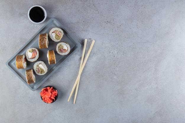 Köstliche sushi-rollen mit thunfisch auf dunklem teller.