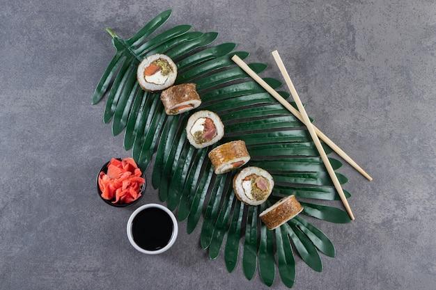 Köstliche sushi-rollen mit thunfisch und eingelegtem ingwer auf grünem blatt.