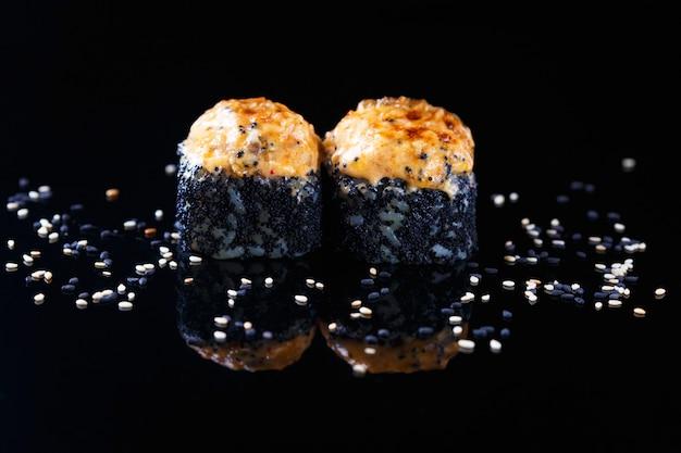 Köstliche sushirolle mit fischen und indischem sesam auf einem schwarzen hintergrund mit reflexion menü und restaurant