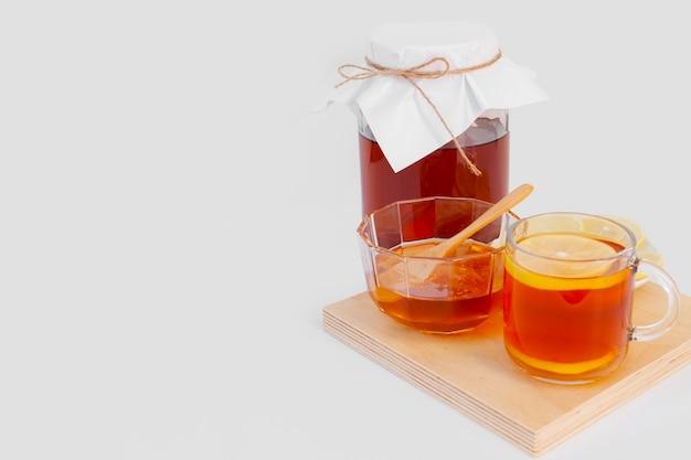 Köstliche tasse tee mit zitrone auf einem hölzernen brett