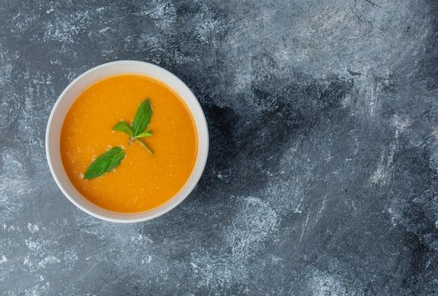 Köstliche tomatensuppe in weißer schüssel.