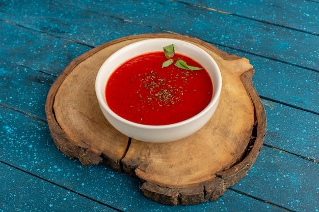 Köstliche tomatensuppe in whtie platte auf blauem, suppenmahlzeit-abendessengemüse
