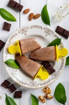 Köstliche und erfrischende schokoladeneis am stiel in einem vintage-teller auf einem weißen holztisch bedeckt mit schokoladenstücken, nüssen, mandeln und blättern aus der natur