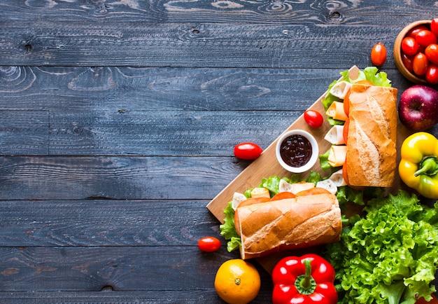 Köstliche und geschmackvolle sandwiche mit truthahn, schinken, käse, tomaten auf hölzernem hintergrund