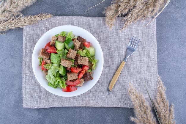 Köstliche und gesunde platte mit hirtensalat garniert mit getrockneter kruste auf einer gefalteten tischdecke mit einer gabel auf marmoroberfläche