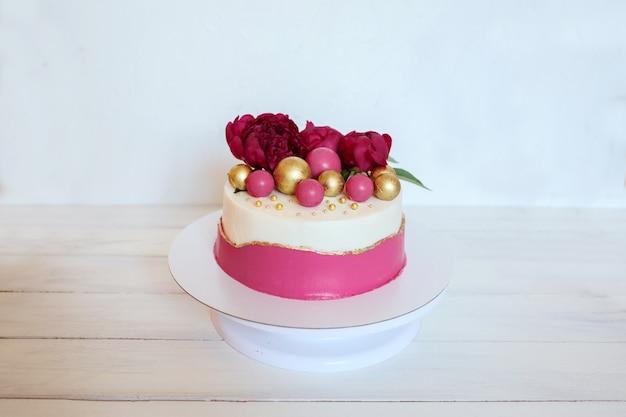 Köstliche und schöne geburtstags- oder hochzeitstorte, verziert mit pfingstrosenblumen und bunter schokolade
