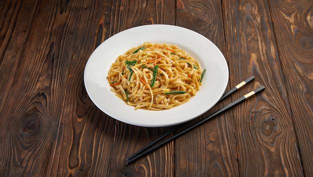 Köstliche und würzige hausgemachte nudel in weißer platte mit schwarzen stäbchen auf holztisch, asiatischer lebensmittelkonzeptkopierraum für menüdesign