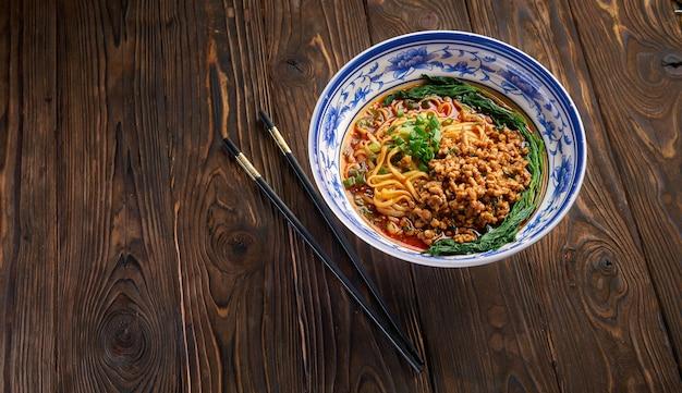 Köstliche und würzige hausgemachte sichuan-reisnudel in traditioneller blauer schale mit schwarzen stäbchen auf holztisch, asiatischer lebensmittelkonzeptkopierraum für menüdesign