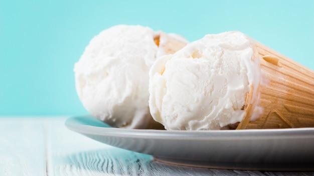 Köstliche vanilleeiskegel, die auf platte legen