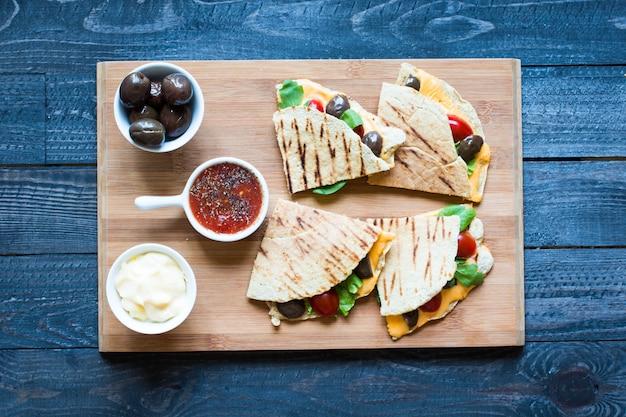 Köstliche vegetarische quesadillas mit tomaten, oliven, safran und cheddar