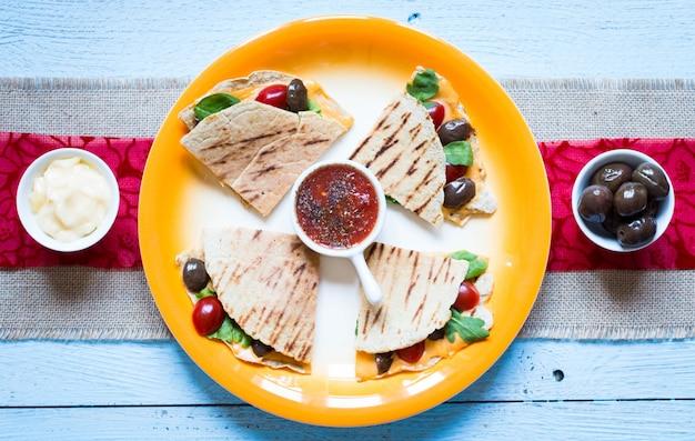 Köstliche vegetarische quesadillas mit tomaten, oliven, saïad und cheddar