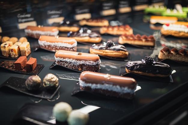 Köstliche verschiedene eclairs und süßigkeiten auf einem schwarzen tisch