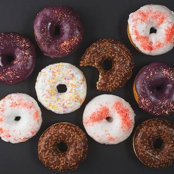 Köstliche verschiedene gebissene donuts mit zuckerglasur auf schwarzem hintergrund