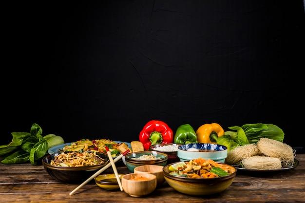 Köstliche vielzahl des thailändischen lebensmittels in den verschiedenen schüsseln mit bokchoy und grünem pfeffer auf tabelle gegen schwarzen hintergrund