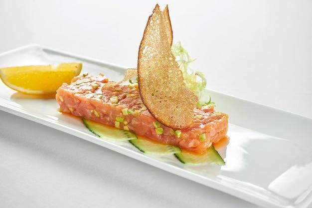 Köstliche vorspeise - lachstartar mit avocado und schwarzem kaviar auf einem weißen teller auf einer blauen tischdecke.