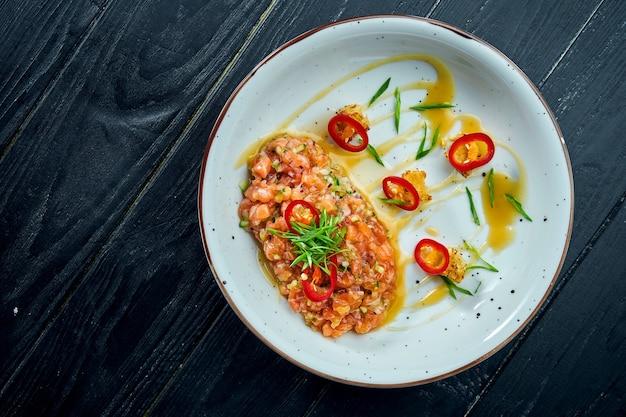 Köstliche vorspeise - lachstatar mit avocado und scharfem chili auf einem weißen teller auf schwarzer holzoberfläche.