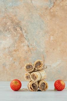 Köstliche waffeln mit zwei roten weihnachtskugeln auf marmorhintergrund. hochwertiges foto