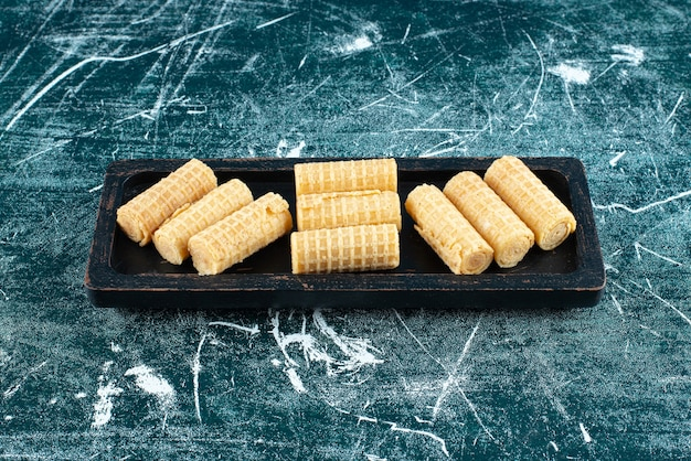 Köstliche waffelröllchen auf schwarzem teller.
