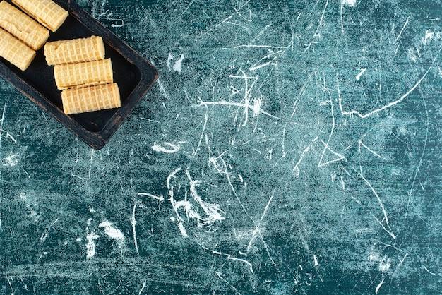 Köstliche waffelröllchen auf schwarzem teller. Kostenlose Fotos