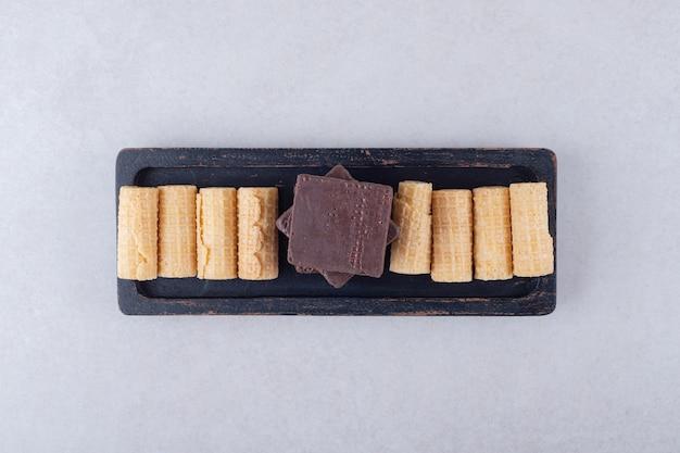Köstliche waffelröllchen und mit schokolade überzogene waffeln auf einer holzplatte auf dem marmor.