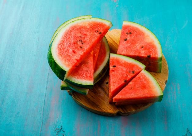 Köstliche wassermelonenstücke auf blauem hintergrund, flach liegen.