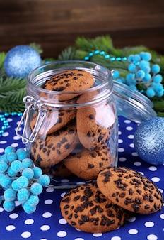 Köstliche weihnachtsplätzchen im glas auf dem tisch auf hölzernem hintergrund