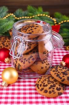 Köstliche weihnachtsplätzchen im glas auf dem tisch auf holzuntergrund
