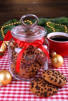 Köstliche weihnachtsplätzchen im glas auf tisch auf holzoberfläche