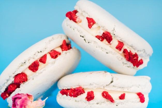 Köstliche weiße makrone mit blumen gegen blauen hintergrund