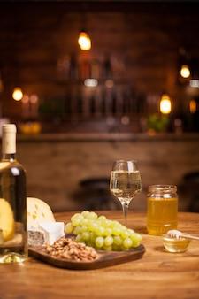 Köstliche weiße trauben auf einer rustikalen holzplatte neben leckeren walnüssen. weinprobe. verschiedene leckere käsesorten.