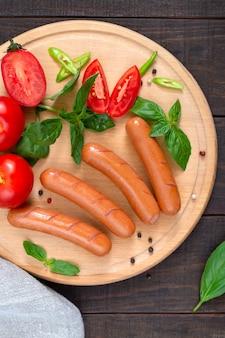 Köstliche würzige hotdogwürste mit frischen tomaten und basilikum auf einem schneidebrett. würstchen zum frühstück. ansicht von oben.
