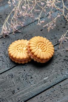 Köstliche zuckerkekse der vorderansicht auf dem süßen nachtisch des dunklen schreibtischkekses