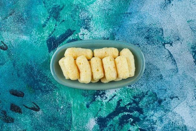Köstliche zuckermaisstangen in einem teller auf dem blauen tisch.