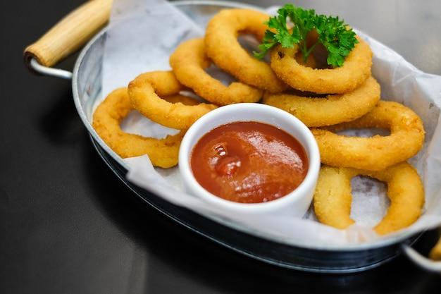 Köstliche zwiebelringe mit tomatensauce dienen auf metallschüssel