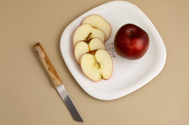 Köstlicher apfel und in weiße platte mit messer und gabel schneiden