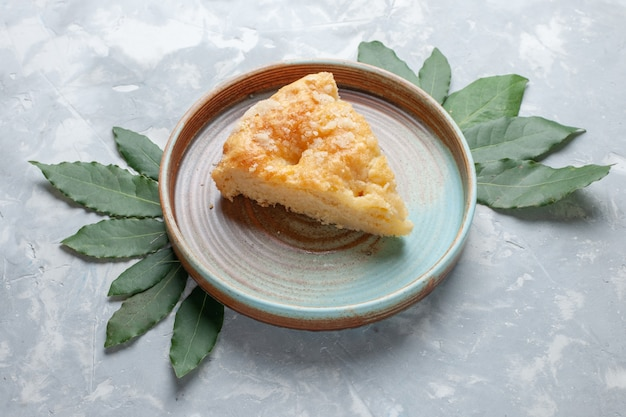 Köstlicher apfelkuchen der halben draufsicht innerhalb des tellers auf dem weißen zuckerkuchenauflauf des weißen schreibtischkuchen-keks