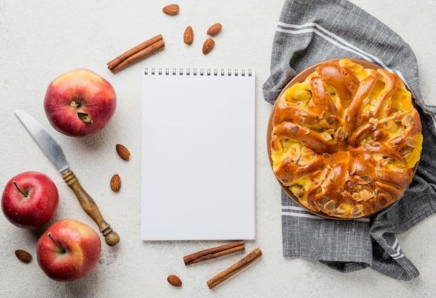 Köstlicher apfelkuchen mit draufsicht des notizblockes