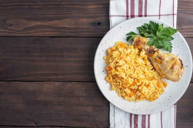 Köstlicher asiatischer pilaw, gedünsteter reis mit gemüse und hühnertrommelstock auf einem teller. rustikaler hölzerner hintergrund. kopieren sie die draufsicht auf den speicherplatz