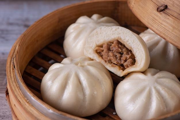 Köstlicher baozi, chinesisches gedämpftes fleischbrötchen ist fertig zum essen auf servierplatte und dampfgarer, nahaufnahme, produktdesignkonzept für kopienraum.