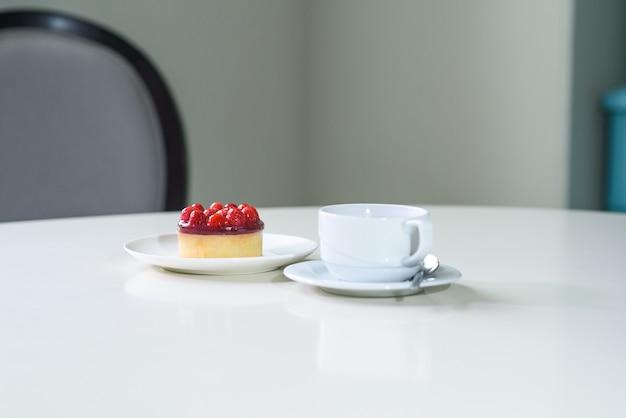 Köstlicher beerentee und tarte mit himbeeren auf einem tisch in einem gemütlichen café