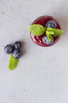 Köstlicher blaubeerensmoothie mit frischen beeren und minze in den glasgefäßen. sommer gesundes getränk.