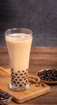 Köstlicher bubble-milchtee mit tapioka-perlenkugel im glas auf holztisch