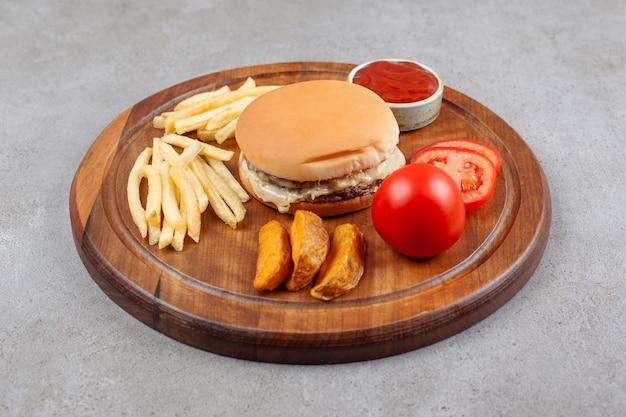 Köstlicher burger mit kartoffelpommes und ketchup auf holzbrett