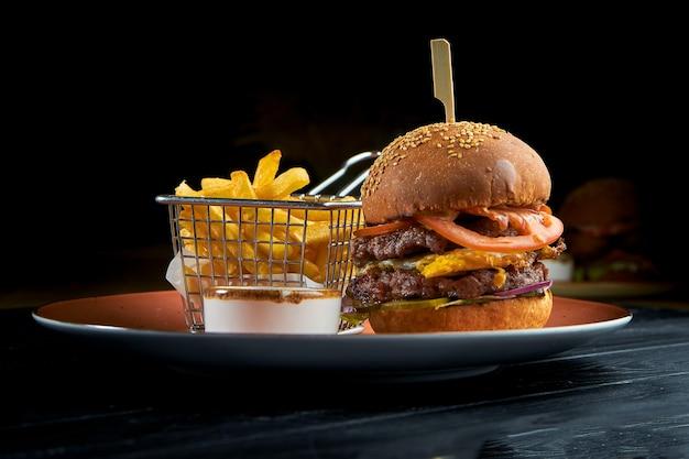 Köstlicher burger mit rindfleisch, tomaten, zwiebeln und gelber sauce, serviert in einem roten teller mit langsamem cole-salat. amerikanisches fast food