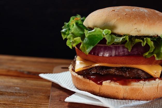 Köstlicher burger mit salat, tomate und roten zwiebeln und speck auf hausgemachtem brot mit samen und ketchup auf einer holzoberfläche und schwarzem hintergrund.