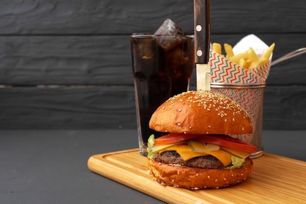 Köstlicher burger und pommes auf holzbrett gegen schwarze vorderansicht