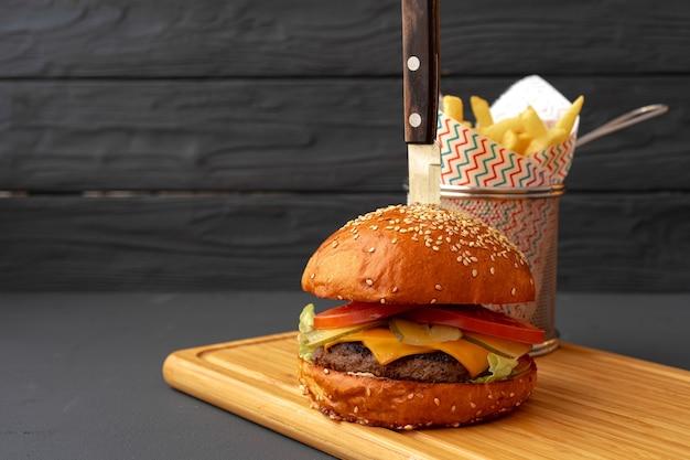 Köstlicher burger und pommes auf holzbrett gegen schwarzen tisch, vorderansicht
